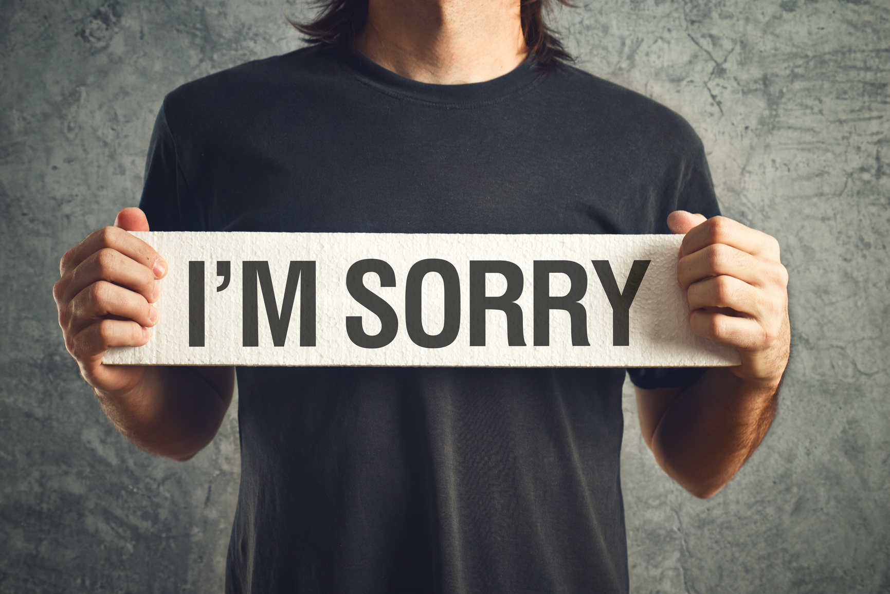 Man holding I am sorry message on white board. remorse concept.